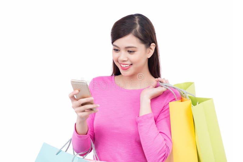 Piękna zakupy kobieta texting na jej telefonie komórkowym, odosobniony ove obrazy royalty free