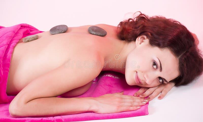 Piękna zdroju kobieta w różowym ręczniku z kamieniami obraz stock
