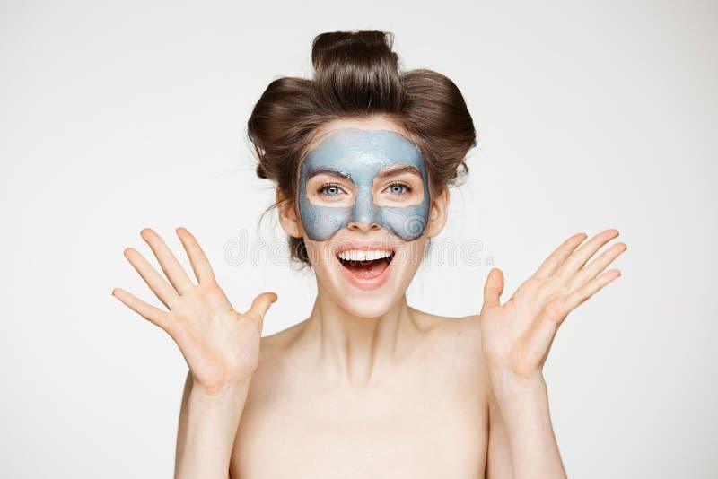 Piękna zdziwiona naga dziewczyna ono uśmiecha się nad białym tłem w włosianych curlers i twarzowej maskowej patrzeje kamerze rozp zdjęcia stock