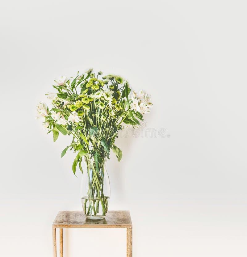 Piękna zieleń kwitnie wiązkę z spada płatkami w szklanej wazie przy biel ściany tłem opracowane do domu żywy wewnętrznego styl re zdjęcie stock