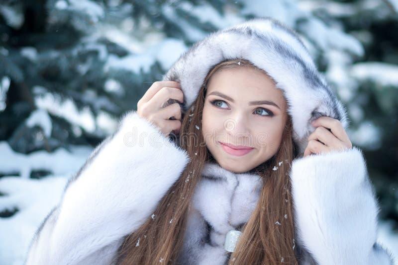 Piękna zimy kobieta w białym wyderkowym futerkowym żakiecie przy bożymi narodzeniami na śnieżnym tle dziewczyny się uśmiecha fotografia stock