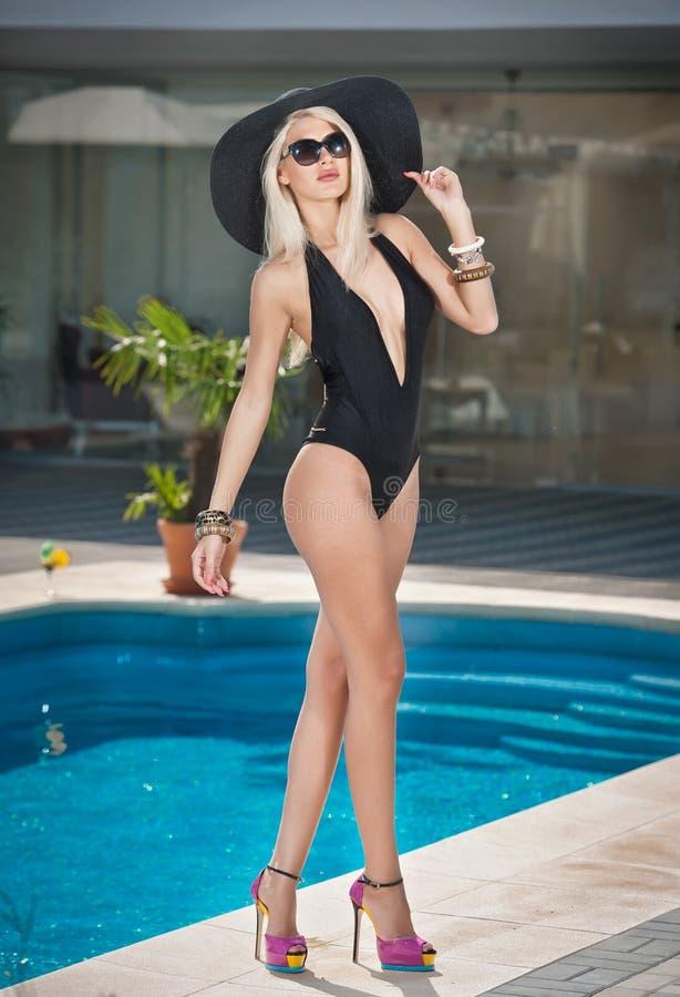 Piękna zmysłowa blondynka z modnymi okularami przeciwsłonecznymi i kapeluszem pozuje blisko basenu Atrakcyjna kobieta w czarnym c zdjęcie royalty free