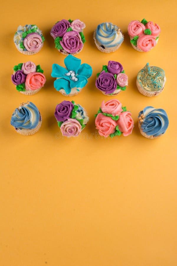 Piękne babeczki dekorowali z kwiatem od kolorowego cukierki obrazy royalty free