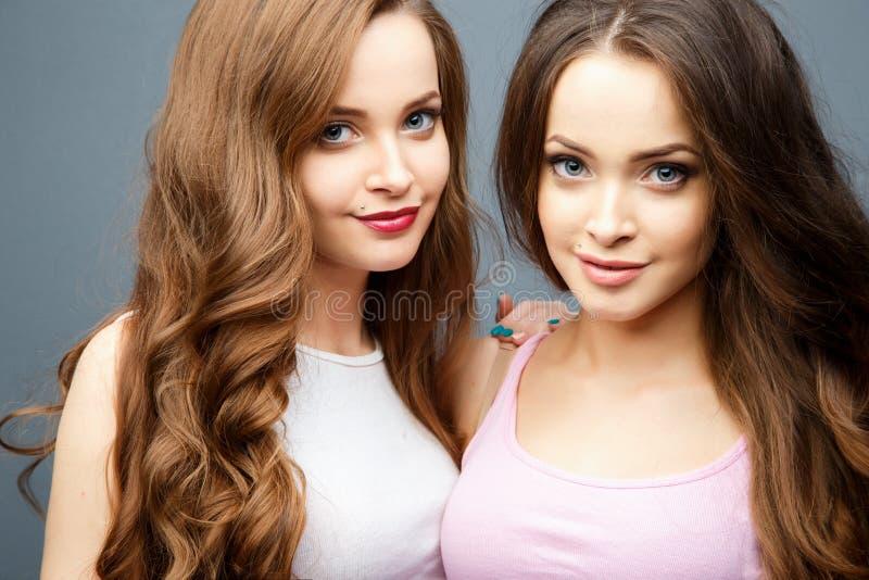 Piękne bliźniak młode kobiety w przypadkowych ubraniach nad popielatym tłem Piękno mody portret obrazy stock