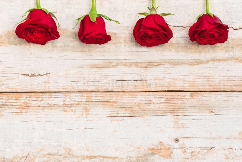 Piękne czerwone róże graniczą na nieociosanym drewnie, romantyczny kwiatu tło dla walentynka dnia lub matka dnia kartka z pozdrow obraz stock