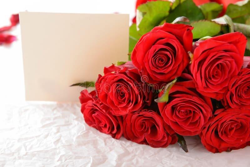 Piękne czerwone róże i karta na kocowanie papierze, zbliżenie zdjęcie stock