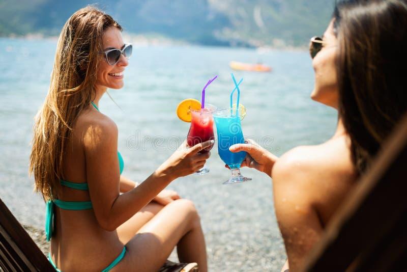 Piękne dysponowane dziewczyny w letnim dniu ma zabawę i koktajle na plaży obrazy stock