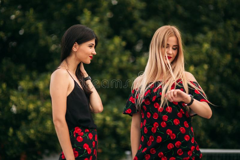 Piękne dziewczyny pozuje dla fotografa Dwa siostry w czerni i czerwieni sukni Uśmiech, słoneczny dzień, lato obrazy stock