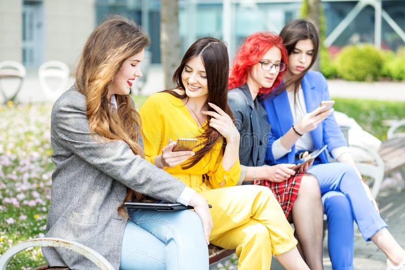 Piękne dziewczyny siedzą z gadżetami na ławce Kobiety komunikują Pojęcie internet, ogólnospołeczne sieci, nauka i zdjęcia royalty free