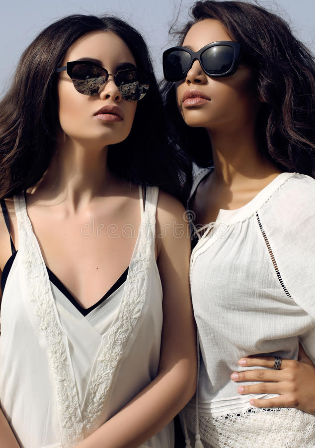 Piękne dziewczyny z ciemnym włosy są ubranym przypadkowy elegancki odzieżowego i okulary przeciwsłonecznych zdjęcie royalty free