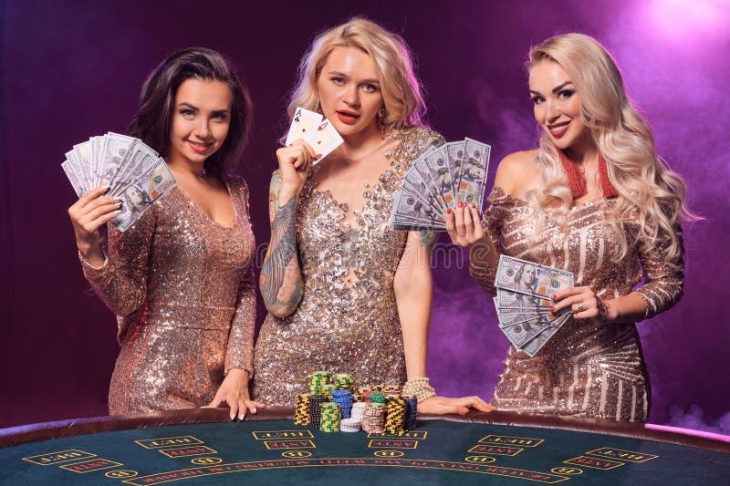 Piękne dziewczyny z doskonalić fryzury i jaskrawy makijaż pozują stać przy uprawia hazard stołem Kasyno, grzebak zdjęcie royalty free