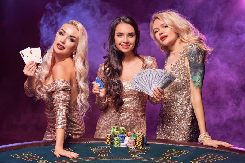 Piękne dziewczyny z doskonalić fryzury i jaskrawy makijaż pozują stać przy uprawia hazard stołem Kasyno, grzebak fotografia royalty free