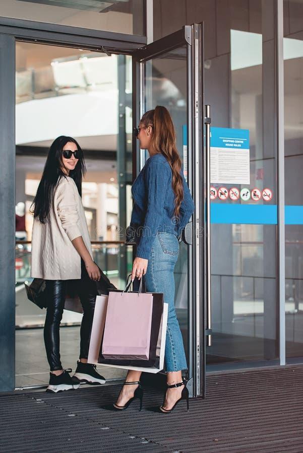 Piękne dziewczyny z papierowymi torbami zbliżają wejście supermarket zdjęcie stock