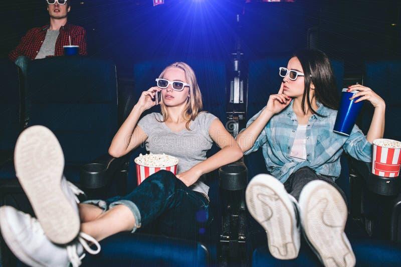Piękne i atrakcyjne dziewczyny siedzą w krzesłach Blondynki dziewczyna opowiada na thhe telefonie Jej przyjaciel jest pokazywać zdjęcia stock