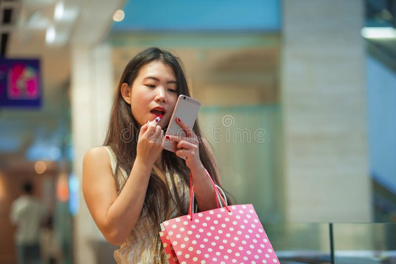 Piękne i szczęśliwe Azjatyckie Chińskie kobiety retuszerki wargi z pomadki makeup patrzeje telefon komórkowego używać je jako lus obraz stock