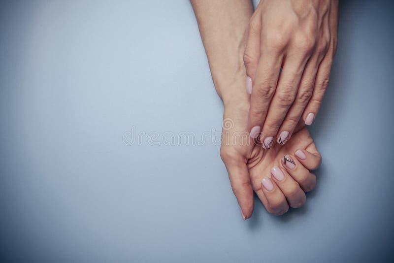 Pi?kne kobiet r?ki i modny manicure na b??kitnym tle z elementami tonowanie zdjęcie royalty free