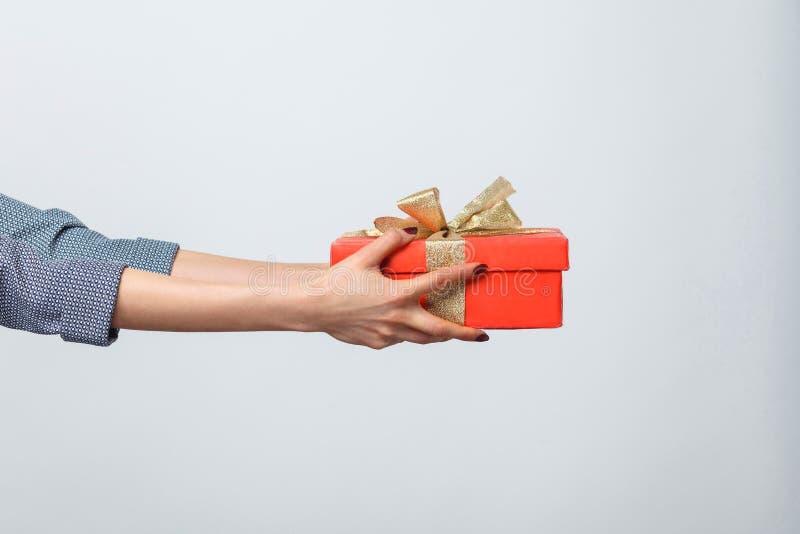 Piękne kobiet ręki trzyma czerwieni pudełko teraźniejszego z żółtym łękiem odizolowywającym na popielatym tle i daje ci zdjęcie royalty free