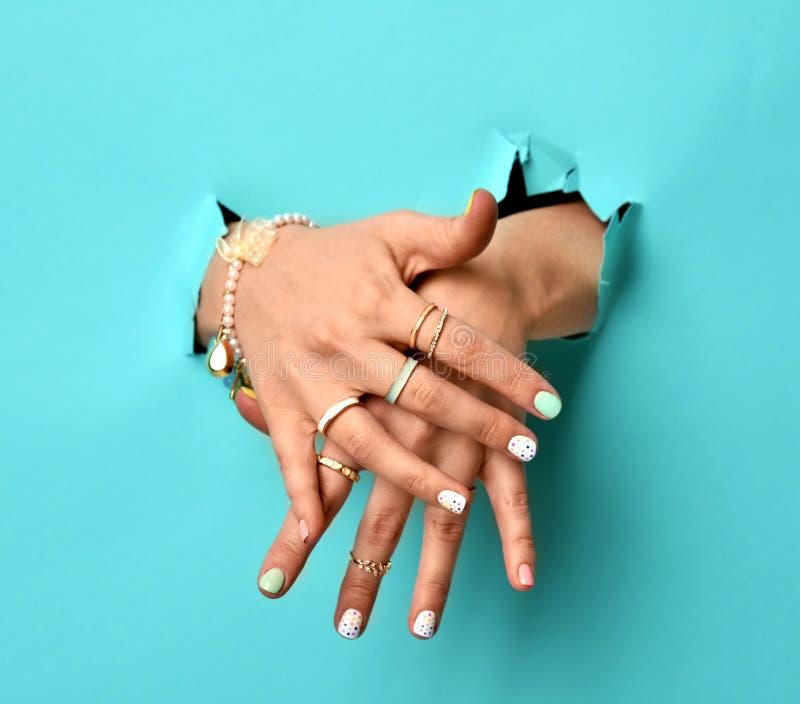 Piękne kobiet ręki z kolor żółty menchii bielem deseniują bransoletki i pierścionki gwoździa srebra i połysku obraz stock