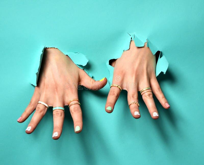 Piękne kobiet ręki z kolor żółty menchii bielem deseniują bransoletki i pierścionki gwoździa srebra i połysku zdjęcia royalty free