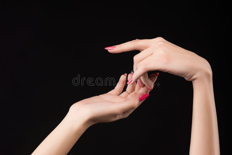 Piękne kobiet ręki z menchiami robią manikiur na gwóźdź odizolowywającym o obrazy royalty free