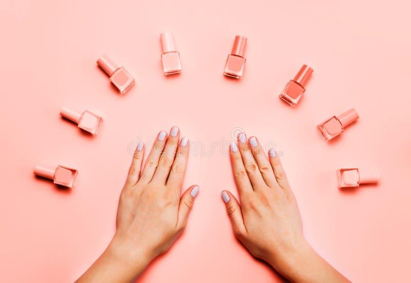 Piękne kobiet ręki z modnym eleganckim manicure'em na modnym Żywym Koralowym tle zdjęcia royalty free