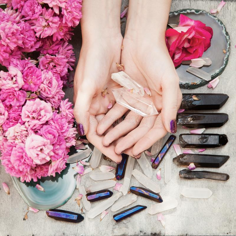 Piękne kobiet ręki z perfect fiołkowym gwozdziem polerują na białym drewnianym tle trzyma małych kwarcowych kryształy zdjęcie stock