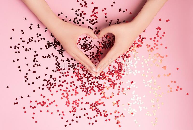 Piękne kobiet ręki z wibrującymi czerwonymi sercowatymi confetti nalewali na różowym tle Mieszkanie nieatutowy Miłość i świętowan zdjęcie stock