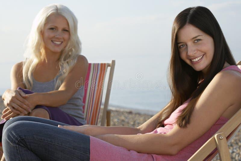 Piękne kobiety Siedzi Na Deckchairs Przy plażą zdjęcia stock