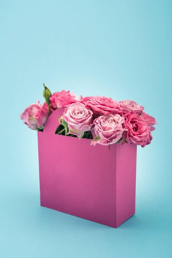 Piękne kwitnienie menchii róże w dekoracyjnej papierowej torbie układali odosobnionego na błękicie zdjęcie stock