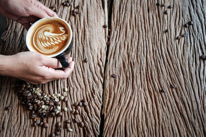 Piękne latte ręki trzymają na starej drewnianej podłoga zdjęcia royalty free