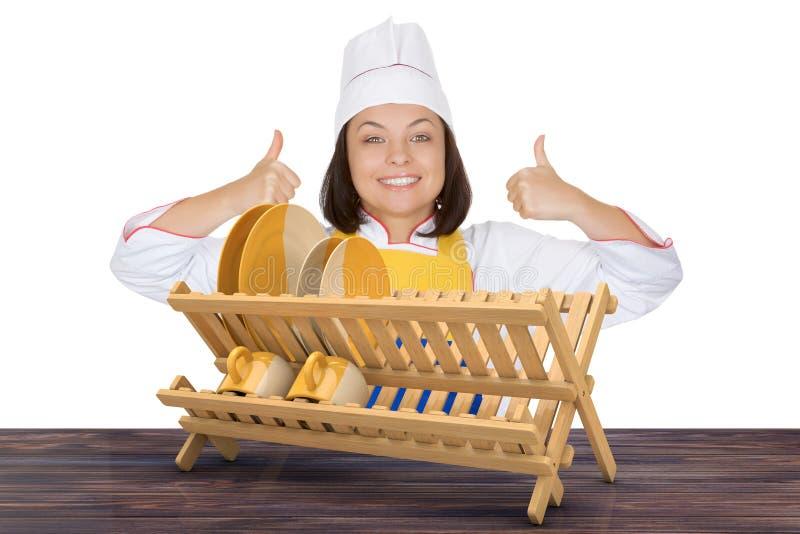 Piękne młoda kobieta szefa kuchni przedstawienia aprobaty zbliżają Bambusowych Kuchennych Di fotografia stock