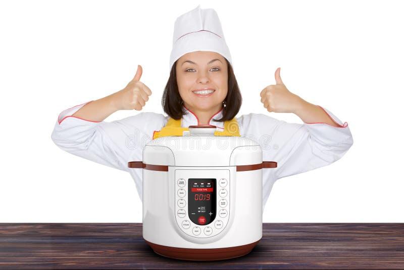 Piękne młoda kobieta szefa kuchni przedstawienia aprobaty zbliżają Nowożytnego Elektrycznego M fotografia stock
