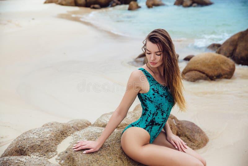 Piękne młode brunetek kobiety w błękitnym bikini pozuje na plaży w kręcenie łupie pokazują osła Seksowny wzorcowy portret z zdjęcia stock