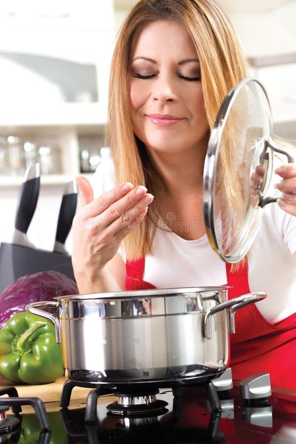 Piękne młode kobiety gotuje jedzenie w kitche i bada obrazy royalty free