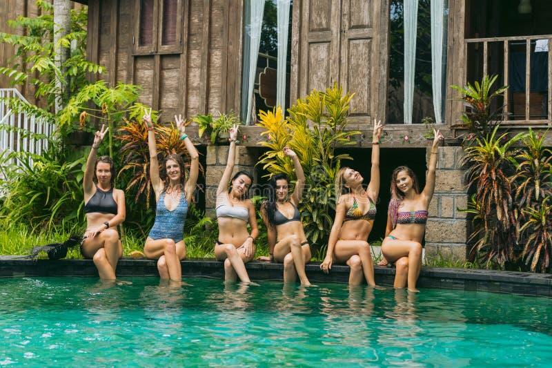piękne młode kobiety w swimwear obsiadaniu przy basenem i ono uśmiecha się fotografia stock