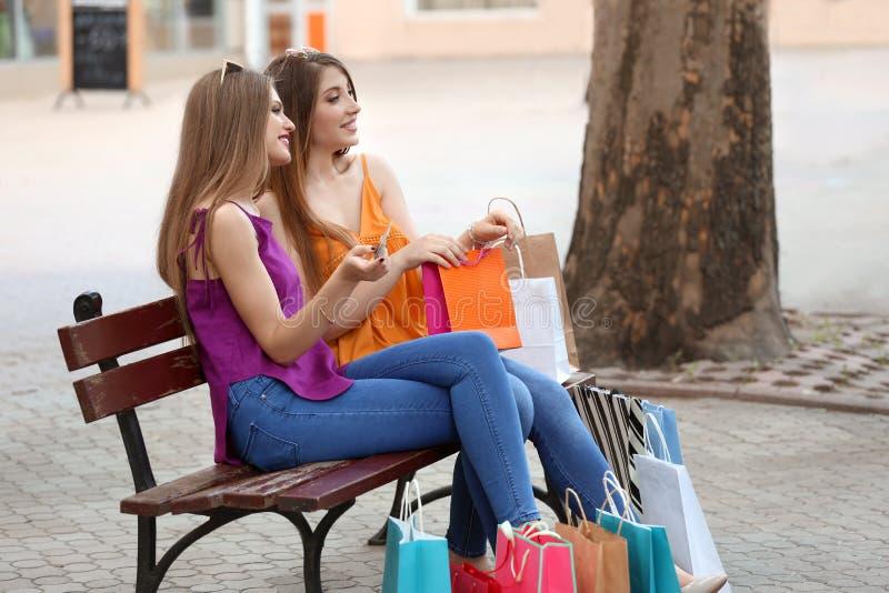 Piękne młode kobiety z torbami na zakupy i karty kredytowej obsiadanie na ławce outdoors zdjęcia stock