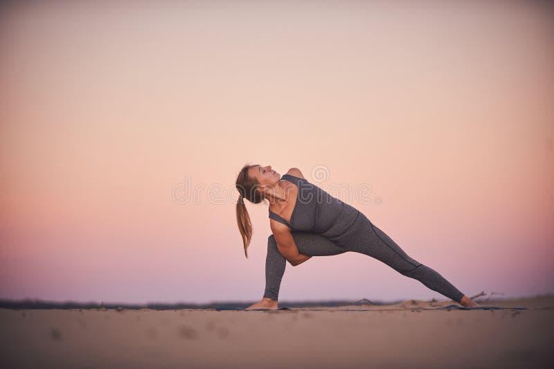 Piękne młodych kobiet praktyki przekręcają joga asana Parivritta Parshvakonasana w pustyni przy zmierzchem obraz royalty free