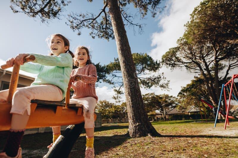 Piękne małe bliźniacze siostry bawić się na seesaw obrazy stock