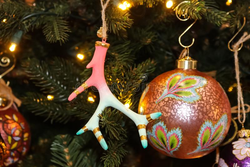 Piękne menchie i turkusowi Bożenarodzeniowi ornamenty wliczając jeleniego rogu z złocistym podstrzyżeniem na choince - selekcyjna zdjęcie stock