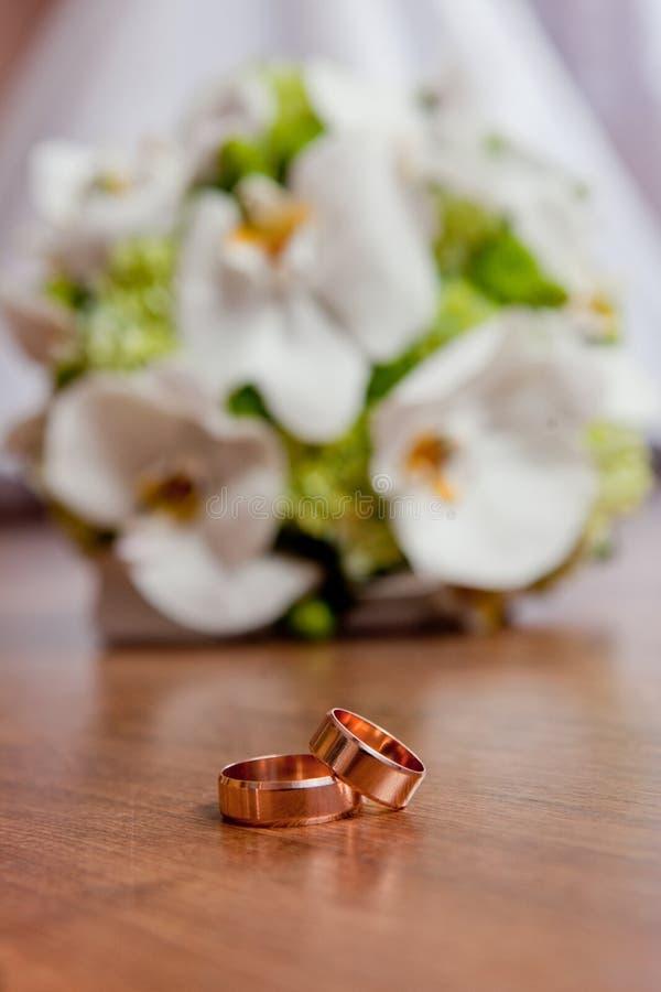 Piękne obrączki ślubne kłamają na stole przeciw tłu bukiet kwiaty zdjęcia stock