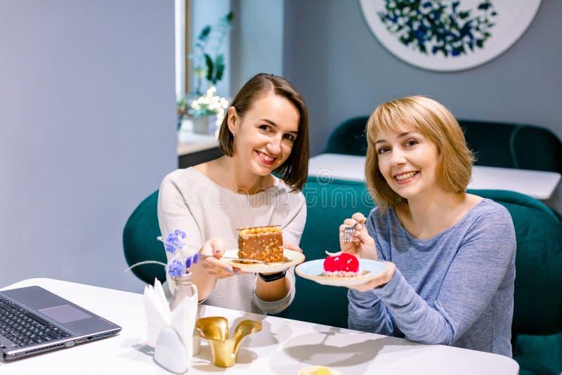 Piękne przyjaciółki dzielące się smacznymi, kolorowymi ciastkami w kafejce, uśmiechające się Przyjaźń kobiet zdjęcie royalty free