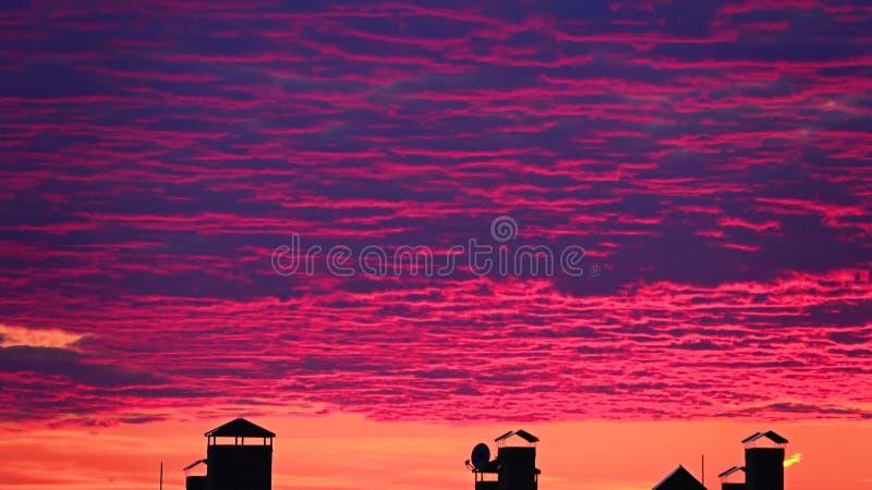 Piękne różowe zmierzch chmury ruszają się nad grodzkimi dachami zawodnik bez szans zdjęcia stock