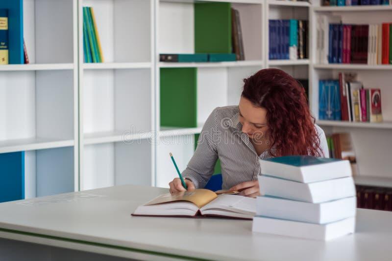 Piękne rudzielec dziewczyny writing notatki w notatniku z stosem obraz stock