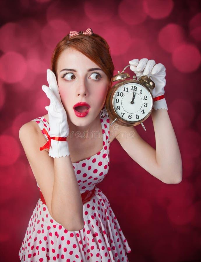Piękne rudzielec kobiety z zegarem. obrazy royalty free