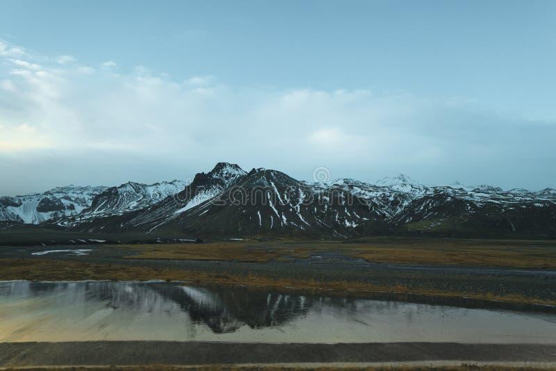 piękne skaliste góry z śniegiem odbijali w spokój wodzie obrazy royalty free