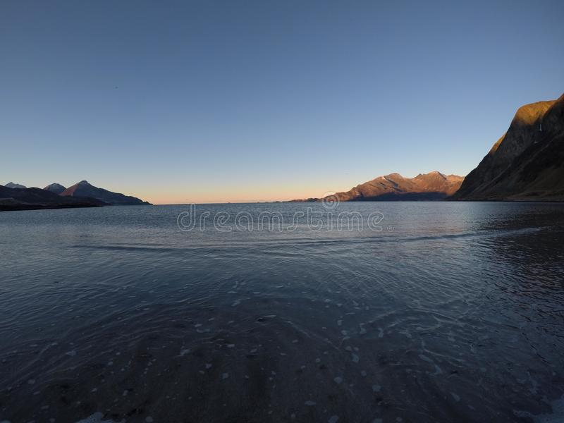 Piękne spokojne błękit fala uderza białą marznącą piaskowatą plażę w opóźnionej jesieni w arktycznym okręgu z głęboką górą i otwa obraz stock