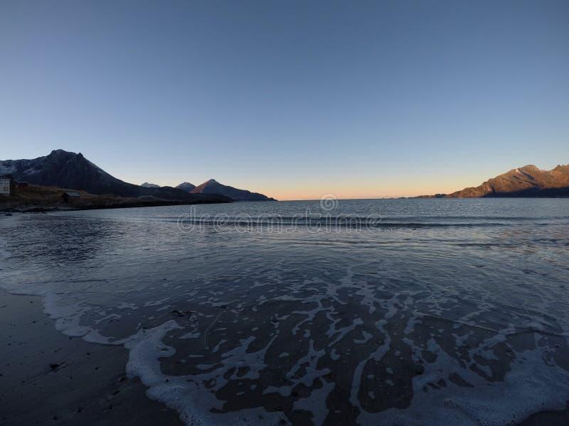 Piękne spokojne błękit fala uderza białą marznącą piaskowatą plażę w opóźnionej jesieni w arktycznym okręgu z głęboką górą i otwa zdjęcie royalty free