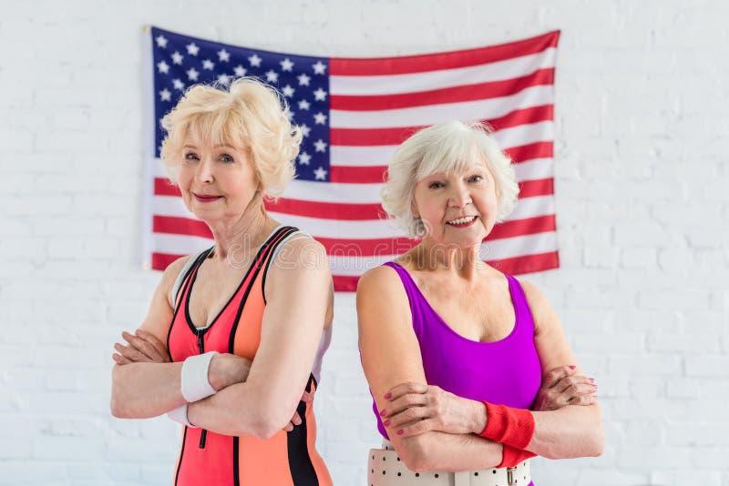 piękne sporty starsze kobiety stoi z krzyżować rękami i ono uśmiecha się przy kamerą przeciw fotografia stock
