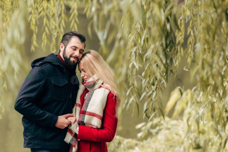 piękne szczęśliwe potomstwo pary mienia ręki i pozycja w jesieni wpólnie zdjęcie stock
