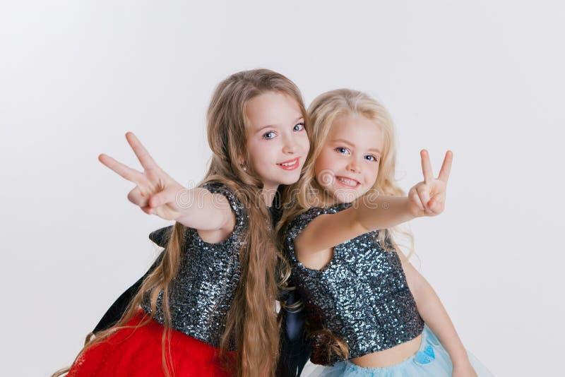Piękne twq małe dziewczynki z kędzierzawymi blondynek fryzurami na wakacyjnym przyjęciu w sukni z cekinami i czarną kurtką fotografia stock